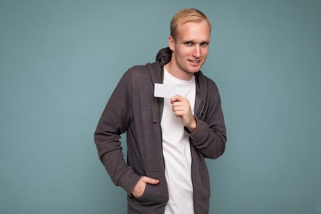 회색 스웨터와 흰색 티셔츠를 입은 잘생긴 금발 남자는 카메라를 바라보는 신용카드를 들고 파란색 배경 벽에 격리되어 있습니다.