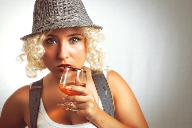 コニャックビジネススタイルを飲む帽子のハンサムなブロンドの女性赤い口紅を持つ若いブロンドの女性
