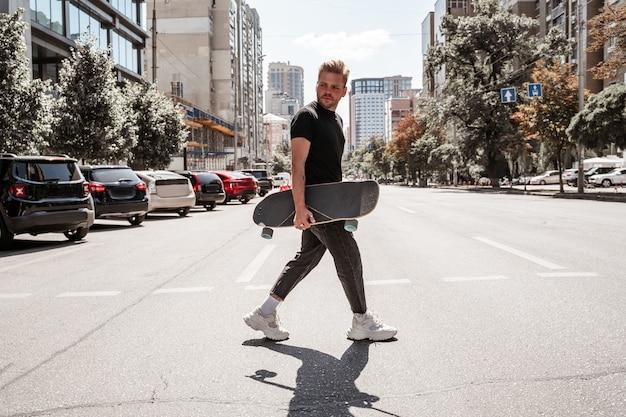 잘생긴 금발의 청년은 차가 주차된 번화한 도시 거리를 가로질러 나무 롱보드를 들고 도시 건물 배경에서 잔인하게 진지해 보입니다. 야외 레저 개념입니다. 도시 스포츠.