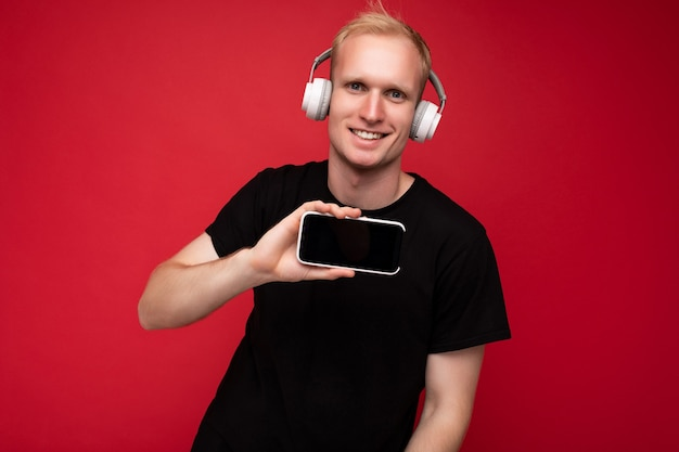 Handsome blonde young man wearing black tshirt and white headphones standing isolated over red