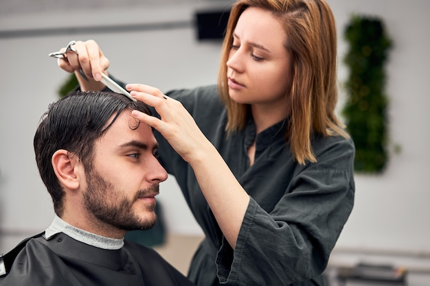 Handsome blue eyed man sitting in barber shop. hairstylist hairdresser woman cutting his hair. female barber.