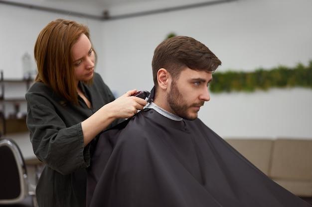 理髪店に座っているハンサムな青い目の男。ヘアスタイリスト美容師女性が髪を切っています。女性の床屋。
