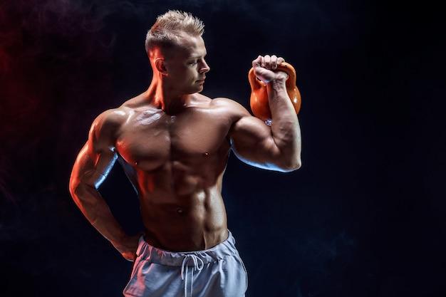 케틀벨과 삼각근, 어깨 근육을위한 운동을하는 잘 생긴 보디.