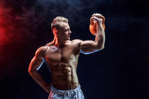 ケトルベルで三角筋、肩の筋肉の運動をしているハンサムなボディービルダー。