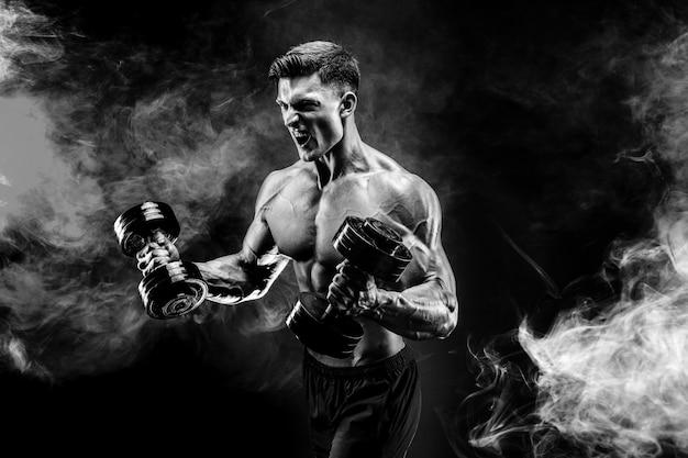 Handsome bodybuilder doing exercise with dumbbell.  smoke
