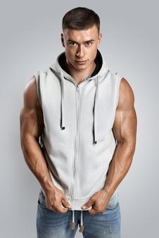 Handsome bodybuilder wearing gray sleeveless hoodie