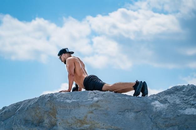 屋外でポーズをとる完璧な筋肉の体を持つハンサムなボディービルダー。黒い帽子をかぶった裸の胴体を持った強い男が立って、目をそらしている。