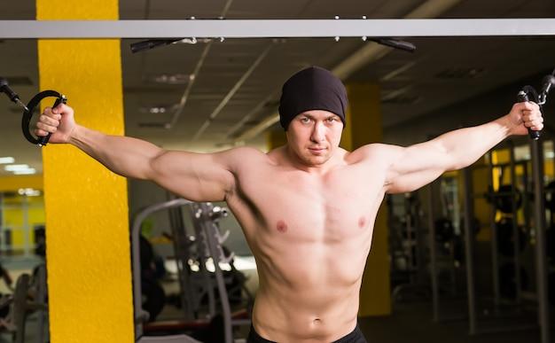 Красивый культурист тренируется в тренажерном зале