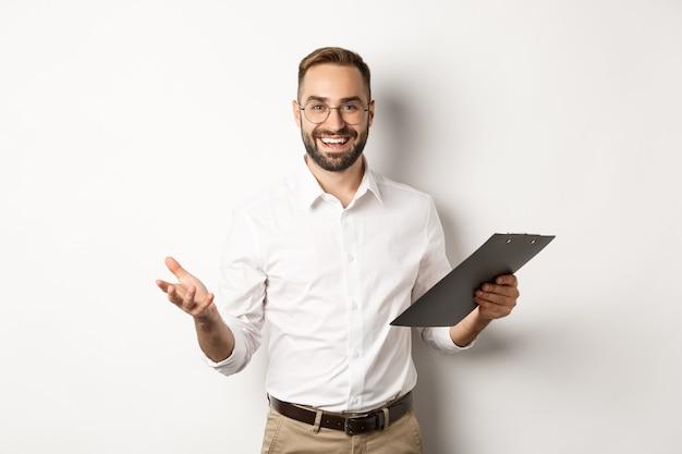 ハンサムな上司は満足そうに見え、クリップボードを持ってあなたを賞賛し、立っています