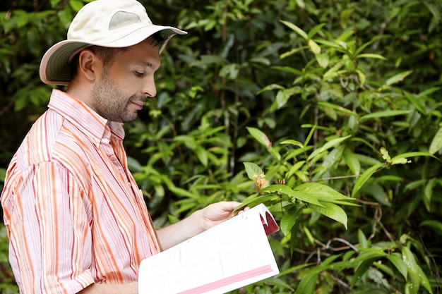 Bello botanico con la barba incolta che indossa una camicia a righe che tiene manuale o guida in una mano e pianta verde con fiori in un'altra, studiandone le caratteristiche con sguardo felice e gioioso.