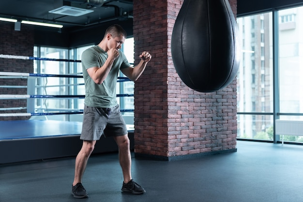 Handsome boxer. handsome boxer wearing sport suit and black sneakers training hard before important competition