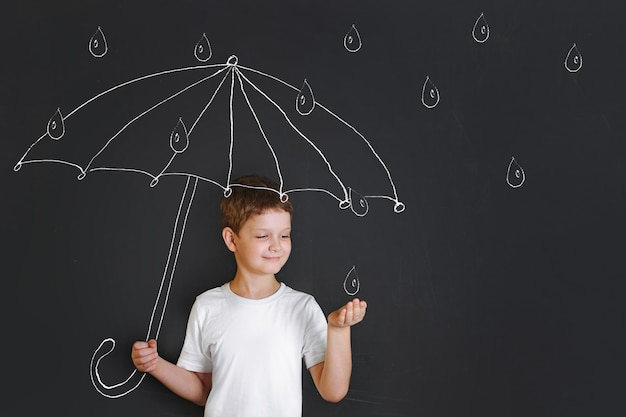 Handsome boy under chalk drawing umbrella