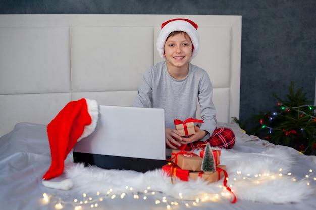 산타 모자를 쓴 잘생긴 소년은 집에서 침대에 누워 있는 동안 노트북 화면을 봅니다. 겨울의 아늑한 저녁, 온라인 편지 산타클로스, 친구들과의 온라인 커뮤니케이션.
