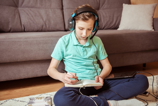 Красивый мальчик делает домашнее задание в наушниках и с планшетом