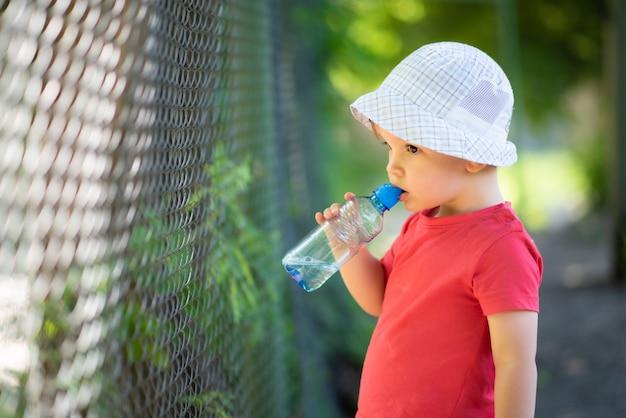 Красивый мальчик пьет чистую воду из бутылки в солнечный день на улице