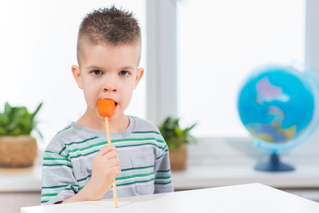 家で棒で新鮮なニンジンを食べるハンサムな男の子。子供は自分の部屋で野菜を食べています。