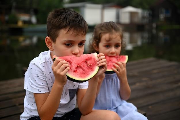妹の隣に座って、おいしい甘いジューシーなスイカのスライスを食べるハンサムな男の子。田舎の桟橋で夏の日を楽しんでください。