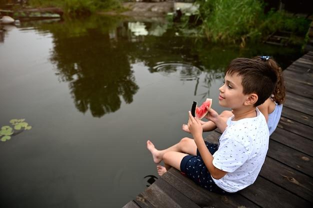 スイカを食べて、日没で美しい夏の日を楽しんで、湖に足を沈めたまま桟橋に座って、夏休みの間に美しい自然と睡蓮を賞賛するハンサムな男の子
