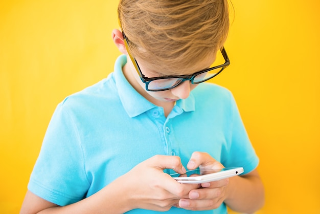 Красивый мальчик в очках играет на планшете