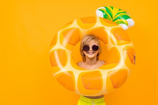 Красивый мальчик в плавках держит резиновое кольцо, улыбается и жестикулирует на оранжевом