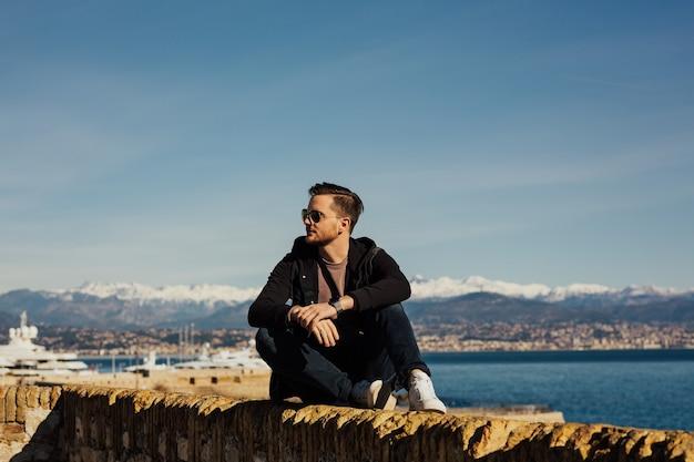 ハンサムな男の子は石の上に座って、海の水の中の船を見ています。