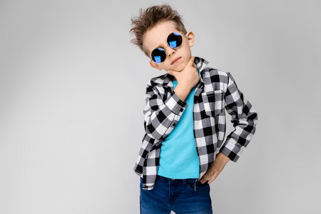 A handsome boy in a plaid shirt, blue shirt and jeans stands. the boy is wearing round glasses. red-haired boy holds his hand to his chin