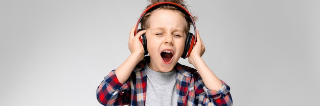 A handsome boy in a plaid shirt, gray shirt and jeans stands. a boy in red headphones sings a song.