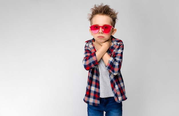A handsome boy in a plaid shirt, gray shirt and jeans stands. a boy in red sunglasses. the boy holds his hands in his throat.