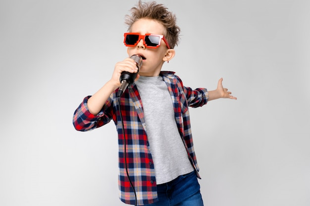 A handsome boy in a plaid shirt, gray shirt and jeans stands. a boy wearing sunglasses. red-haired boy sings into the microphone