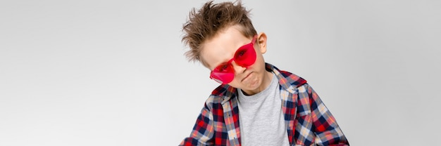 A handsome boy in a plaid shirt, gray shirt and jeans stands on a gray background. a boy in red sunglasses. the boy is pulling his hands forward.