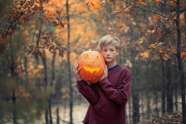 Handsome boy posing at park with halloween pumpkin.