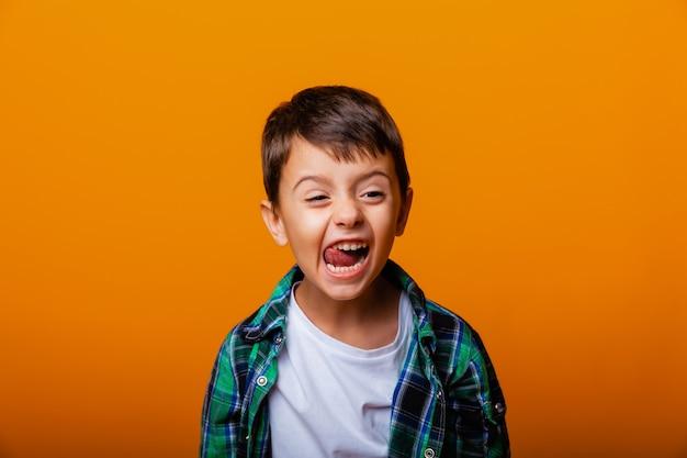 舌を見せて、黄色の背景で楽しんでいるハンサムな男の子。白人の感情的な少年。