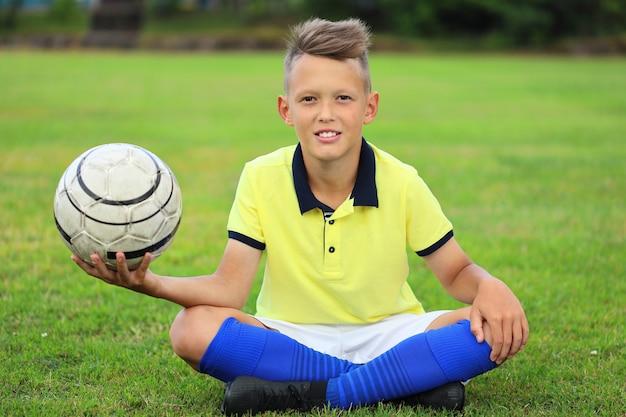 Красивый мальчик футболист, сидя на футбольном поле