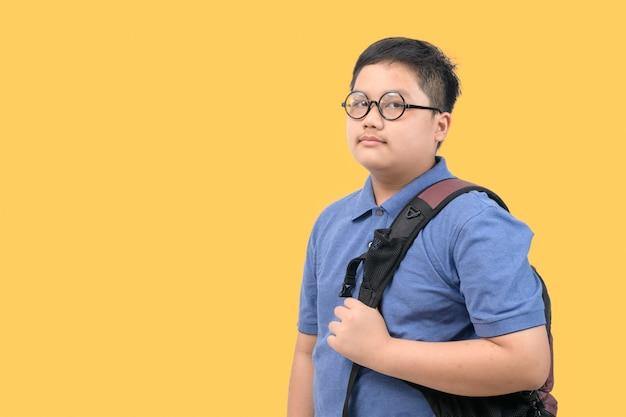 黄色の背景に分離されたランドセルを運ぶハンサムな男の子の学生、学校に戻るコンセプト。