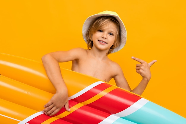 Handsome boy in swimming trunks holds a rubber mattress, smiles and gesticulates isolated on orange