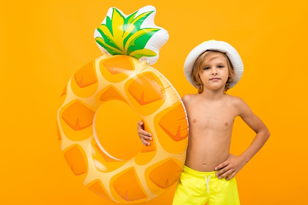 Handsome boy in swimming trunks holds a rubber ring, smiles and gesticulates isolated on orange