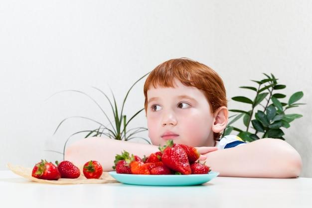 빨간 머리를 가진 잘 생긴 소년은 잘 익은 달콤한 딸기, 디저트 또는 다른 음식을 위해 딸기를 가진 소년을 먹는다.