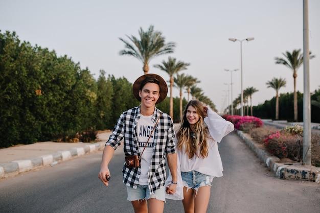 レトロなカメラを持つハンサムな男の子は、エキゾチックなヤシの木が付いている通りに白いシャツで愛らしいガールフレンドと一緒に歩きます。ボーイフレンドと一緒に時間を費やして笑顔の少女の肖像画