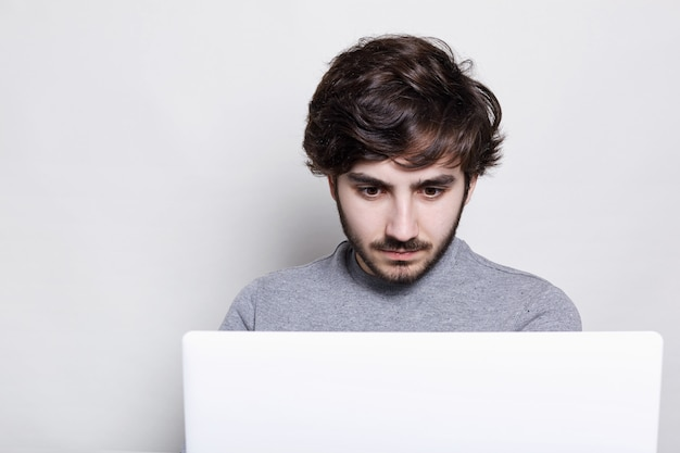 Handsome boy with stylish hairstyle and trendy beard looking with astonishment into the screen of his laptop computer