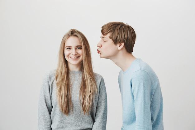 Красивый парень просит поцелуй, девушка улыбается в брекетах