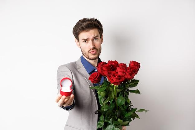 Красивый парень в костюме с просьбой выйти за него замуж, стоя с красным букетом роз и обручальным кольцом, глядя в камеру, умоляя, стоя на белом фоне.
