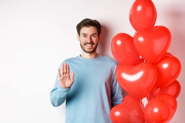 Handsome boyfriend saying hello, bring romantic red heart balloons on date, waving hand and smiling, standing on white