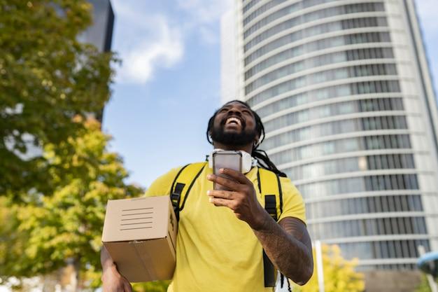 Красивый бразилец с дредами доставщик с коробкой, в наушниках улыбается, глядя на свой смартфон, чтобы найти, фокусируется на лице телефона не в фокусе