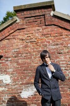 古い家の背景、結婚式の日、肖像画に立っているハンサムな新郎。