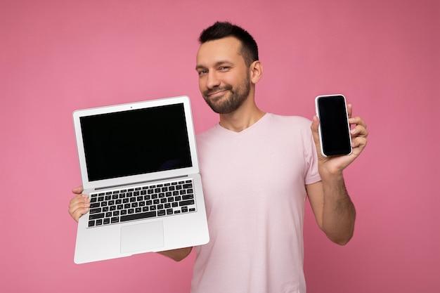 노트북 컴퓨터와 격리 된 분홍색 배경에 티셔츠에 카메라를보고 휴대 전화를 들고 잘 생긴 brunet 남자.