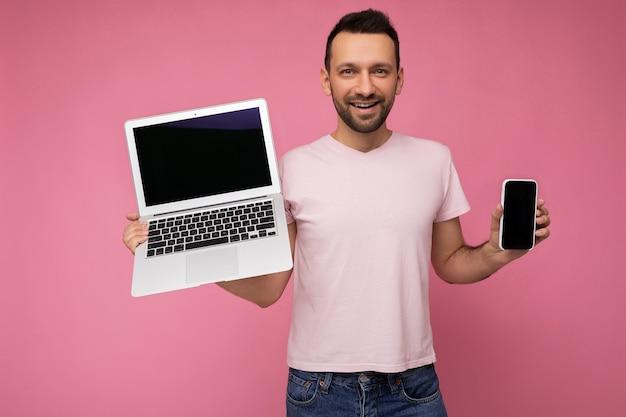 노트북 컴퓨터와 휴대전화를 들고 있는 잘생긴 브루넷 남자는 고립된 셔츠를 입고 카메라를 쳐다보고 있다