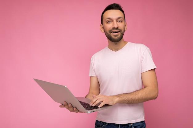 노트북 컴퓨터를 들고 티셔츠에 카메라를보고 키보드에 입력 잘 생긴 brunet 남자