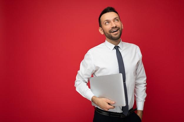 Красивый брюнет, держащий портативный компьютер, глядя вверх в белой рубашке и галстуке на изолированном красном