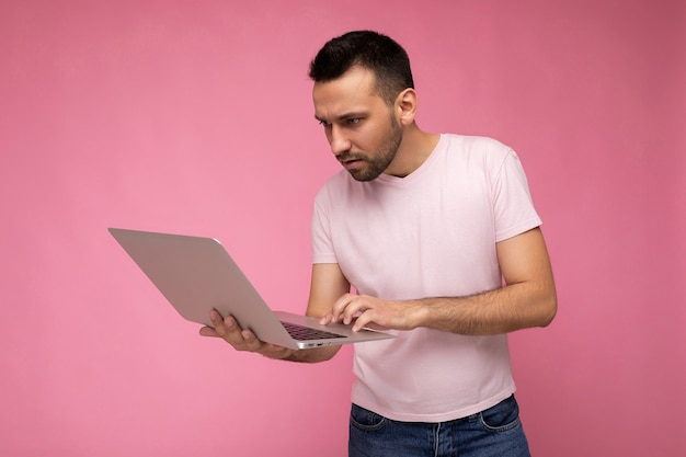 Handsome brunet man holding laptop computer and typing on the keyboard looking at netbook monitor in t-shirt