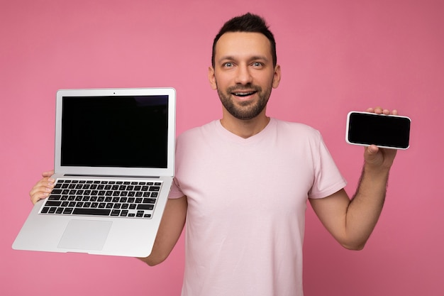 Handsome brunet unshaven man holding laptop computer and mobile phone looking at camera in t-shirt on isolated pink background.
